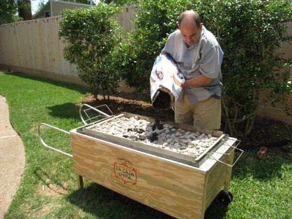 Roberto Guerra loads charcoal into the top of a La Caja China.