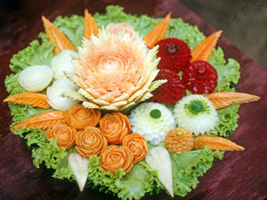 A platter of artistic carved vegetables.
