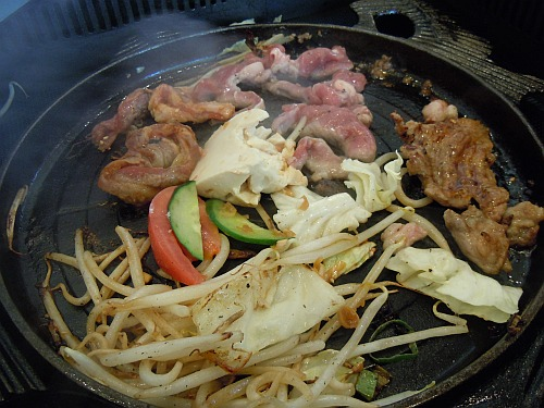 Lamb and vegetables cooking on a Japanese jingisukan griddle.
